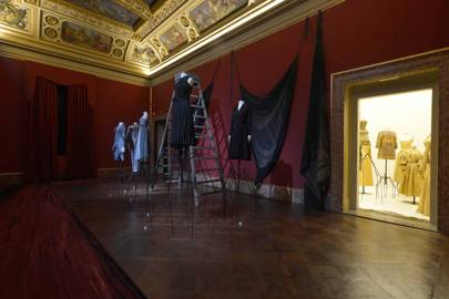 """""""The Threat of Light"""": A display of dresses (by Madame Grès, Gianni Versace, and Issey Miyake) illustrating fabric's sensitivity to sunlight and even moonlight, which """"attacks the blacks of textiles"""". The display is also symbolic of the clothing's life in a museum, kept in dark storage, like """"sleeping beauties""""."""