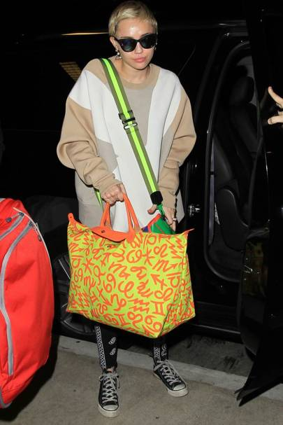 Miley Cyrus with her Longchamp Jeremy Scott limited-edition Le Pliage bag  with zodiac signs 859edb2bab047