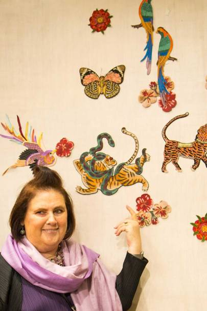 Suzy at a wall panel filled with samples of embroidered motifs, some of which have been used by Gucci
