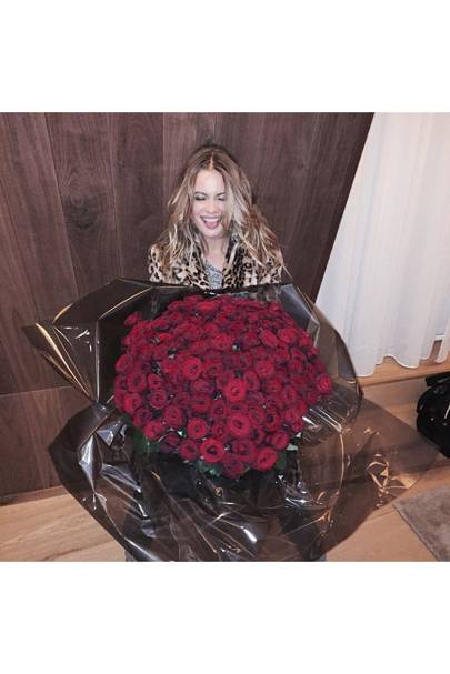 Behati Prinsloo receives a bouquet of flowers from her husband, Adam Levine