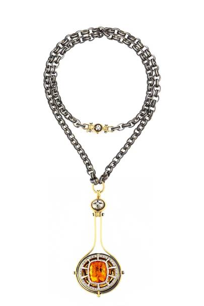 "The ""Pluton"" pendant necklace from the ""Sirius"" collection in open position, revealing a citrine orb"